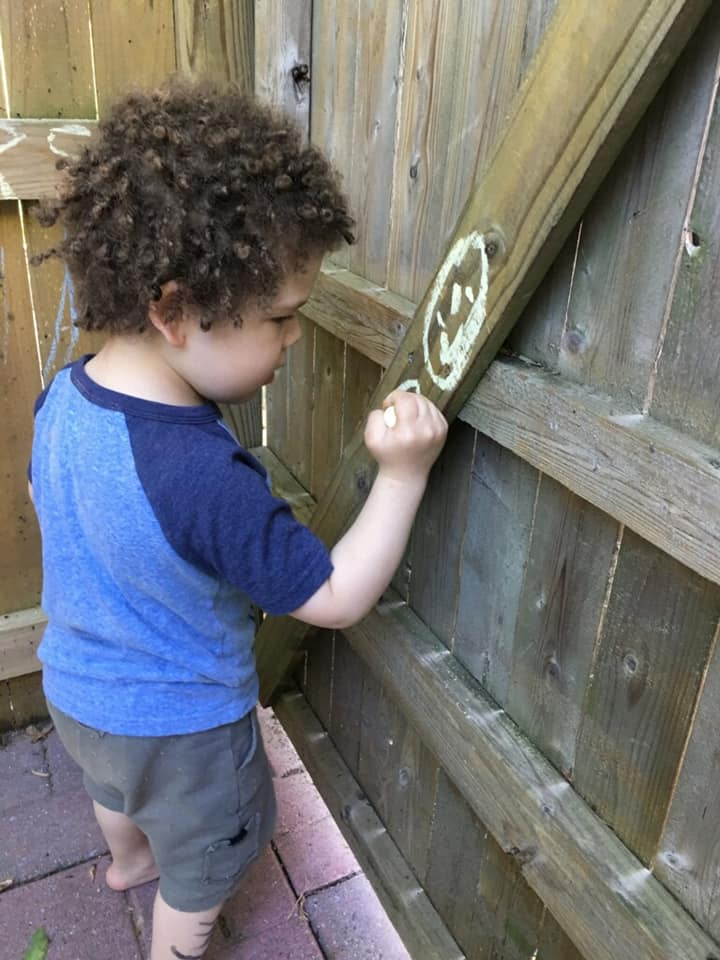 Small child drawing on a fence in chalk